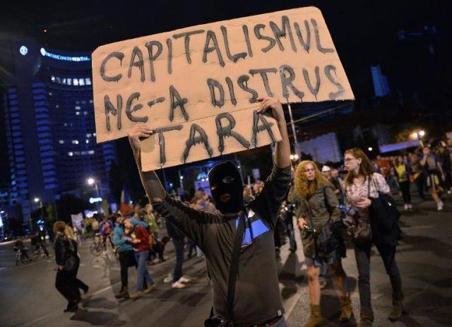 un-roumain-brandit-une-affiche-disant-le-capitalisme-a-detru-Romanie